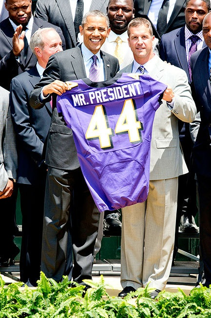Barack Obama poses with Coach John Harbaugh and the entire Baltimore Ravens team as they honor him with a jersey at the White House. Judging by his squint, we'd guess that the President has more than the usual gleam in his eyes.
