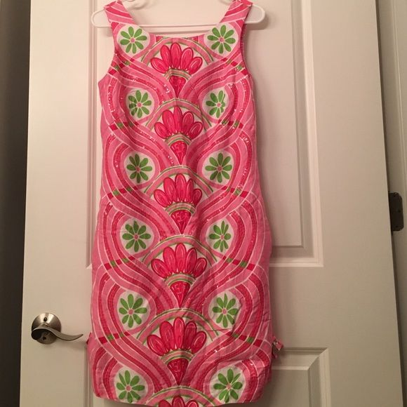 "Lilly Pulitzer Jubilee 50th Anniversary Dress This dress has too many amazing features to count. It features a scoop neckline, a pink and green pattern with the words ""Lilly"" and ""50th Anniversary"" hidden within, side pockets, clear sequins, is fully lined, and is in near perfect condition! This is a limited edition collectors item. Serious offers only! Lilly Pulitzer Dresses"