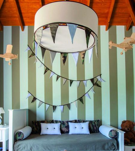 Decoracion cuarto varón. Utilizamos diferentes estampados camuflados, mezclandolos con el colores pastel. Las rayas en la pared verde militar y celeste enmarcan la cama. Avioncitos en el techo y banderines en la lámpara y pared. Estudio Prágmata