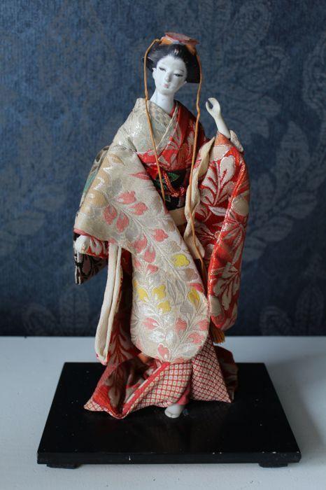 Ningyo pop van een geisha - Japan - ca. 1960  Dit is een zeer mooie en unieke ningyo pop van een geisha in een uchikake of kimono die ook wel voor bruiloften werd gebruikt. Over het geheel verkeerd de pop nog in goede staat maar vertoond wel wat ouderdoms-verschijnselen. Zie ook de foto's voor een goede indruk deze maken deel uit van de omschrijving.Afmeting (inclusief sokkel): 295 cm hoog de sokkel is verder 13 cm diep en 18 cm breed.Wordt goed verpakt verzonden  EUR 1.00  Meer informatie