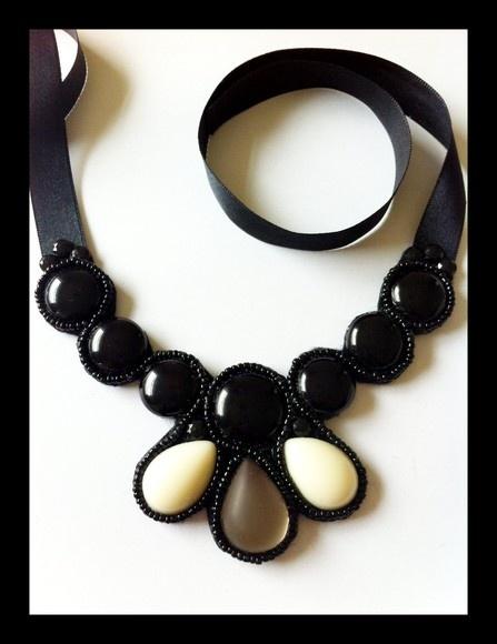 Maxi colar preto, com detalhe em creme e fumê, com pedras de resina e acabamento em feltro. Fita de cetim para amarrar. R$50,00