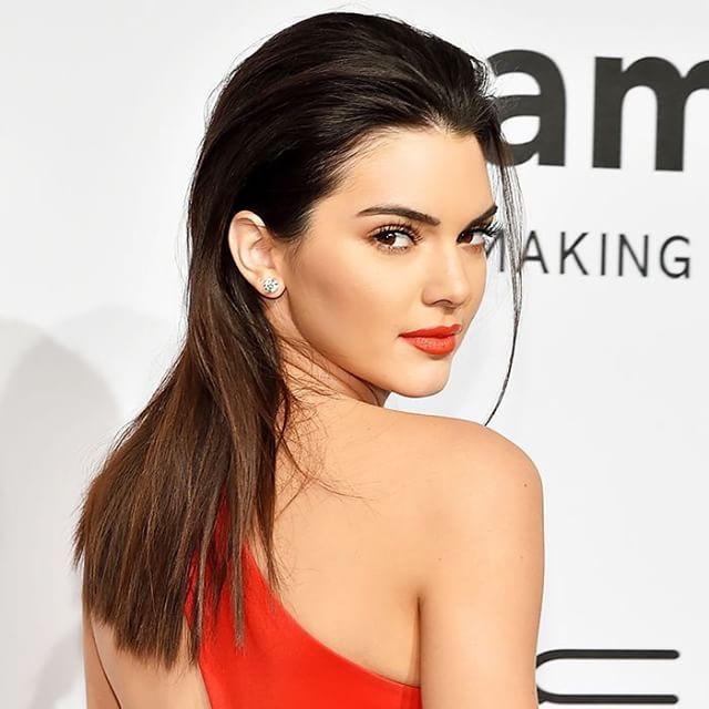 Minimalista com emoção: batom vermelho alaranjado + cabelo liso, solto e penteado para trás na Kendall Jenner | DDB Inspira @diadebeaute