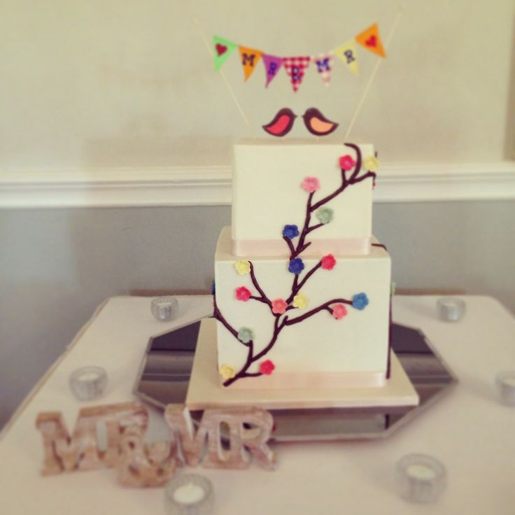 Fun cherry blossom style cake with multi colour blossoms. Chocolate birds and fabric bunting top this cake http://www.kellylou.com