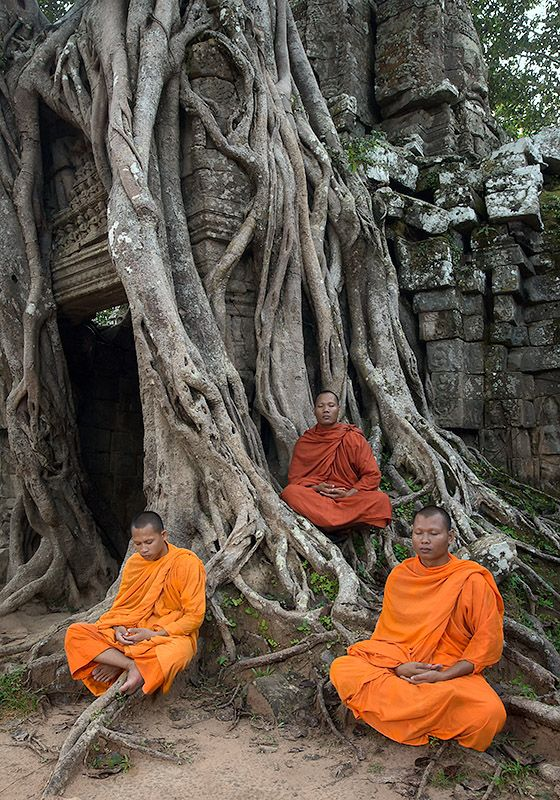 A trio of monks meditating at Angkor Wat Temple in Cambodia.