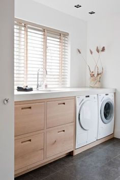 A zen laundry room with wheat colored built-in cabinets and white countertops, appliances, and walls. Interior holiday home by Piet Jan van den Kommer on Behance