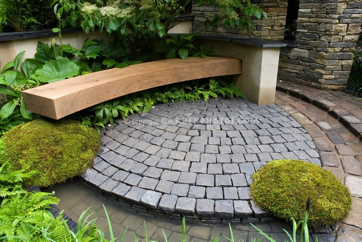 From gardenphotos.com, a photo of what looks to be a cleverly disguised drainage system. The bottom of the photo shows a slightly sloping 'rill' that disappears under the moss circle and the bench - incredibly clever.