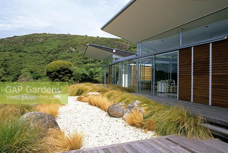 Garden view with boulders and native grasses contrasting with modern building in Piha, New Zealand. Garden Design - Ted Smyth.
