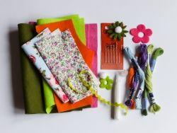1. Potřebujete: kousky tenké plsti a zbytky bavlněných látek s drobným dezénem, bavlnky a vyšívací jehly, květinové výseky, malou bambulku na ocásek, lepidlo na textil, papírovou šablonu zajíce velkou 12 x 19 cm.