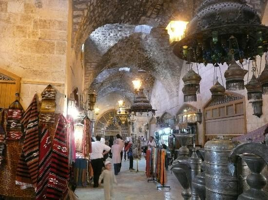 The souk near the Citadel, Aleppo, Syria. 11km maze, exquisitely vaulted alleyways knitted into the most authentic, unspoiled market in the Middle East. Open every day except Fridays, 6000 shops: Lebanese honey, Kashmiri spices, jammed with donkeys.