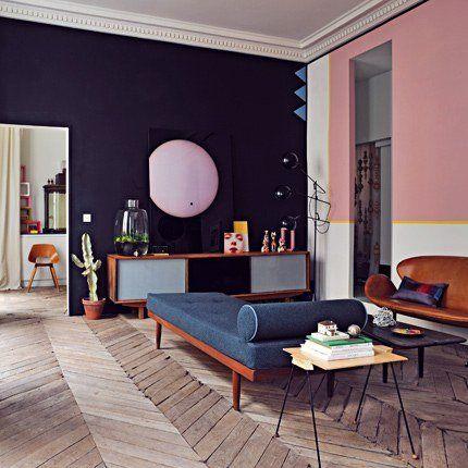 Un salon de style 1950 avec des canapés en cuir d\'Arne Jacobsen, une table basse en bois chinée à Palm Springs, un bahut adossé contre un m...