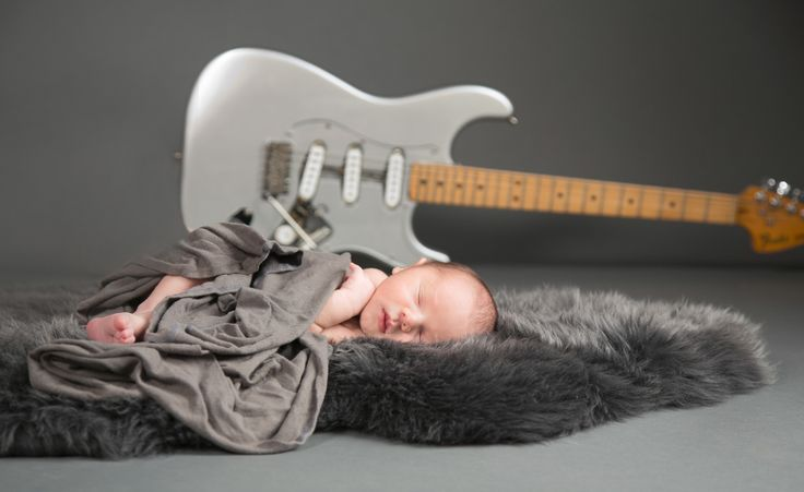 Baby Archer with Daddy's guitar.
