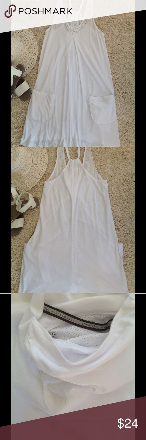 Calvin Klein Beach coverup White coverup featuring two front pockets, one with a mesh zipper lining to hold keys etc. The front top portion has a detailed silver embellishment. Very cute and practical for beachwear. Perfect condition! Machine washable from a smoke free and pet free home. Calvin Klein Swim Coverups