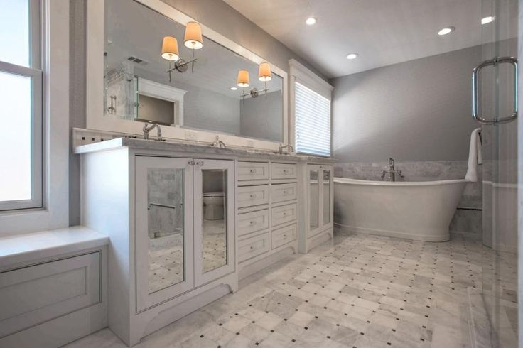 The gray-and-white color scheme of this bathroom creates a clean, spa-like atmosphere. The double vanity provides tons of storage, while the large mirror and mirrored cabinet doors reflect the room's soft light.