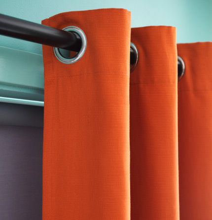 Close-up of orange curtains with eyelet heading