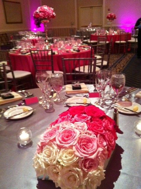 Continue the ombré style in rectangular containers by using 7 shades of pink roses.  A bit of bling added to the table scape with the use of silver linens.