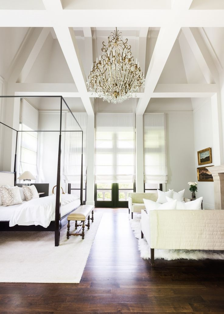 grand bedroom design with four poster bed and elegant chandelier