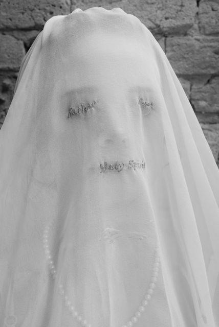 """""""The Bride of Christ"""", a hand-stitched wedding veil with the words """"Father, Son & Holy Spirit"""" embroidered over the eyes and mouth, by artist Haley Nagy."""