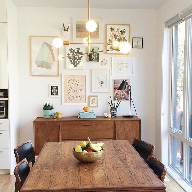 mid century modern dining room design featuring a teak table black leather side chairs a walnut sideboard gallery wall of contemporary pastel artwork