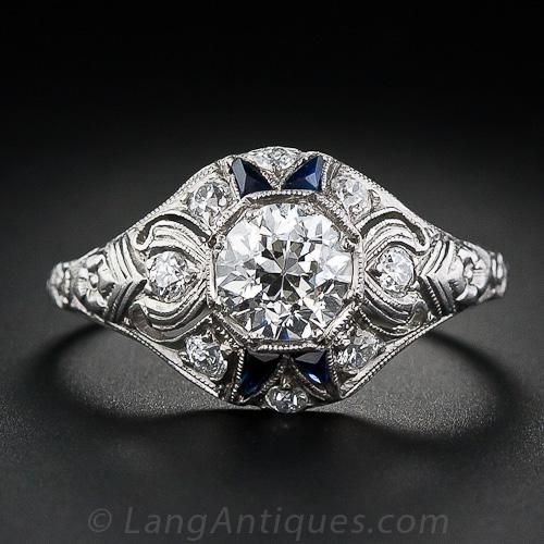 This is a gorgeous, all-original ring from the early Art Deco period. A 1.00 carat European-cut diamond is set in an octagonal bead setting and wrapped with both calibre sapphire and European-cut accent diamonds amidst the scrolled piercework. An orange blossom motif decorates the shoulders. Divine. Ring size 7 1/4.