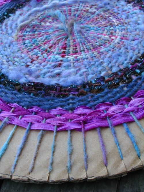 circular weaving w/ cardboard. placemat or pillow front. Use finer yarn @ center, maybe torn fabric strips at outer edge where warp threads get spaced further apart.