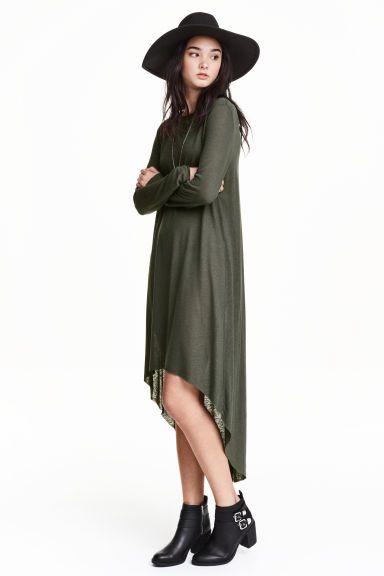 Dżersejowa sukienka: Sukienka z melanżowego dżerseju z domieszką lnu. Długi rękaw, szew z tyłu i niewykończone brzegi. Zaokrąglony dół i nieco dłuższy tył. Bez podszewki.