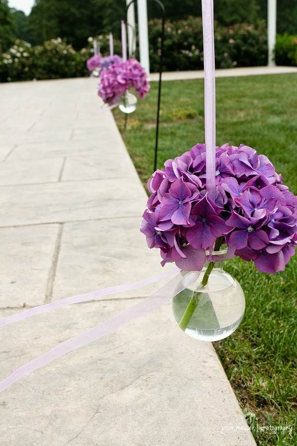 Hanging vases, filled with purple Hydrangeas, made by one of our preferred vendors, A Garden Party, line the aisle leading to our Pergola