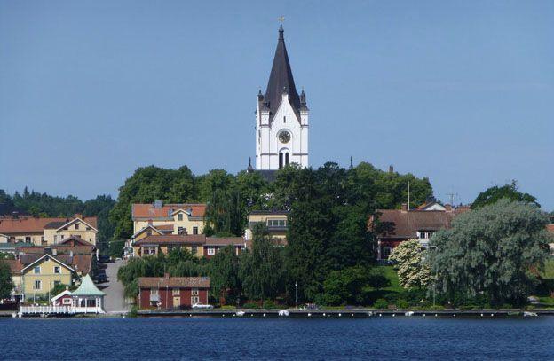 Nora, Sweden. View over the water to the distinctive white church tower - Vy över vatten mot kyrktorn i vitt