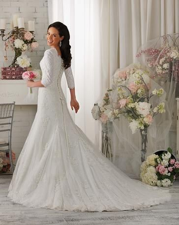 Totally Modest - Cora - Dawning the loveliest lace any bride will fall in love with this fit and flare gown. Highlighted with a scalloped neckline and ¾ length sleeves. Finished with a lace up back. Fabrics: Alencon Lace, Lace, Tulle