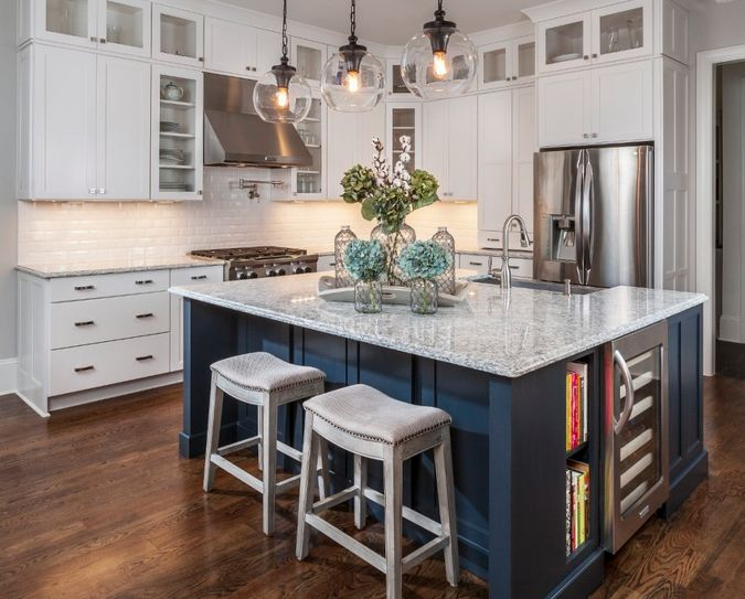 Consider painting your island a different color than your cabinetry. The navy used here warms up all of the white in this kitchen.