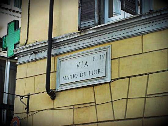 """Via Mario de' Fiori  Nel 1600 in questa via abitava un certo Mario Nuzzi, un discreto pittore di origini abruzzesi, che dipingeva SOLO FIORI ! Sebbene i suoi quadri fossero notevoli, i colori che usava erano  di scarsa qualità, in quanto con il tempo molti di essi si ingrigivano o la pittura si rovinava del tutto, a Roma quindi aveva iniziato a circolare la battuta: """"li fiori dipinti da Mario se sò ammosciati come quelli veri"""" !"""