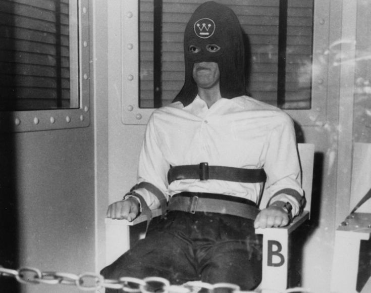 Macabre was Weegee's specialty. Case in point, the photographer took this shot of an American prisoner strapped into a chair in a gas chamber as he is sentenced to death. The prisoner's black hood carrries a Westinghouse Electric Company logo.