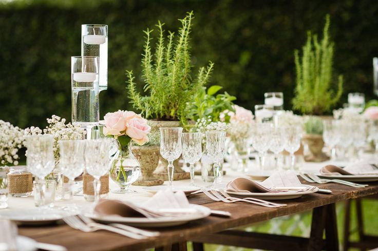 Wooden wedding day table with antique pink roses, pots of herbs, cream linen and vintage crystal glasses. Wedding day at Villa Nozzole. Tuscany, Italy