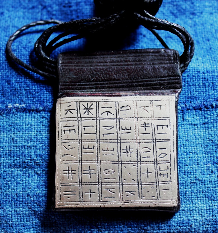 Africa | Tuareg Gri Gri amulet on dark coloured leather with Tifinagh signs. | Tifinagh is the written language of the Tuareg. | Tuareg wear this to protect themselves from bad spirits.