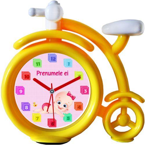 Ceas Bebe fetita cu numele ei    Ceas de perete cu un bebe fetita, o ratusca si cifre in forma de cuburi de joaca. Poate fi personalizat adaugand numele ei. Ceasul este in forma unei biciclete haioase. Poate fi setata alarma.