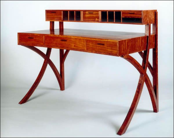 Fine Custom Woodworking - Tiger Desk. Woodworking designer. Shown in bubinga with ebony handles; 56″ x 26″ x 42″. Has four secret compartments and carved pen storage in middle drawer; they are hand dovetailed. Legs are bent laminated. #woodworking