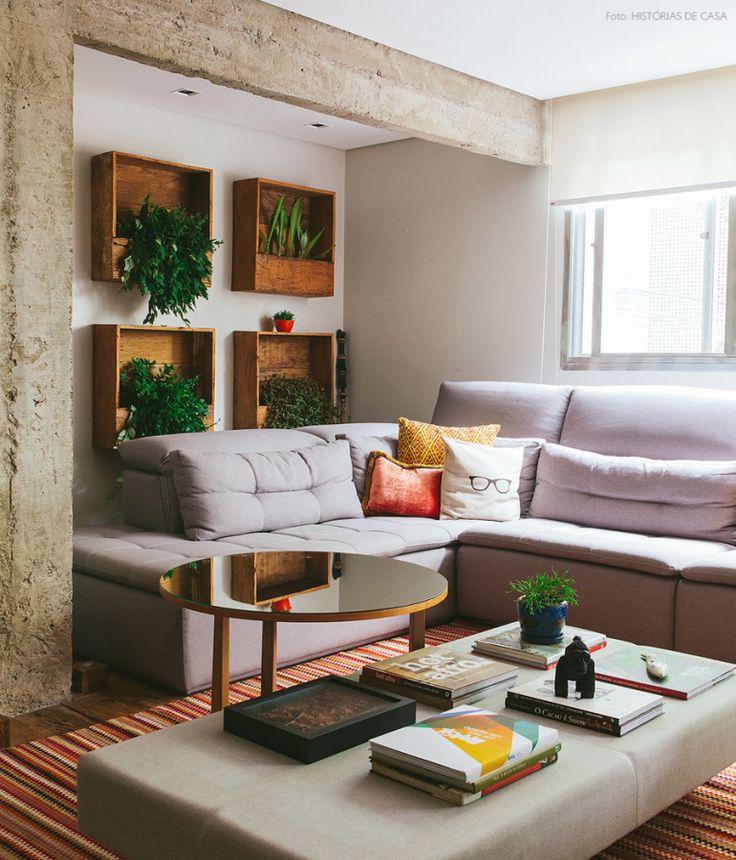 Concreto, madeira de demolição, plantas e tons quentes nessa sala de estar integrada à cozinha.