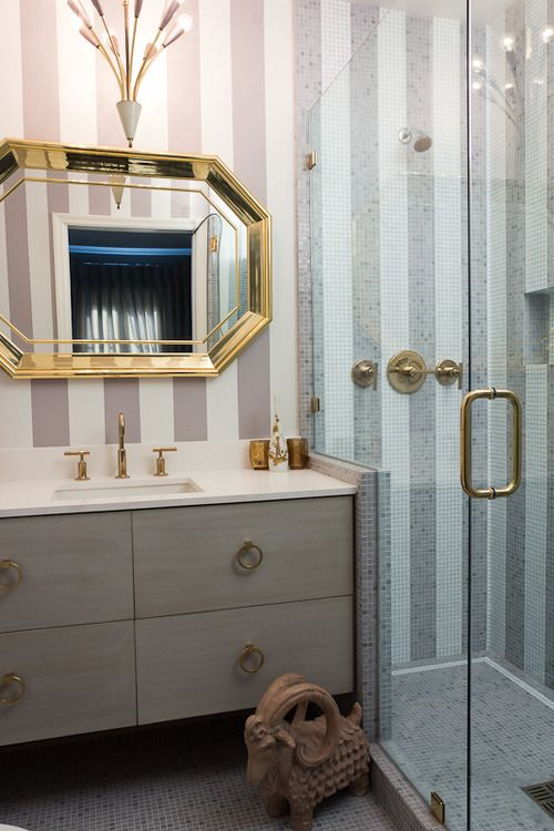 A return to brass fixtures and fittings? Warm metal with cool gray-colored cabinetry and mosaic tile - one color on the floor, two in stripes on the shower walls.
