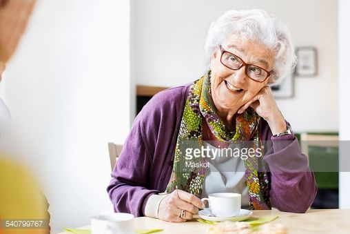 Stock Photo : Happy senior woman looking at friend while having coffee at breakfast table in nursing home