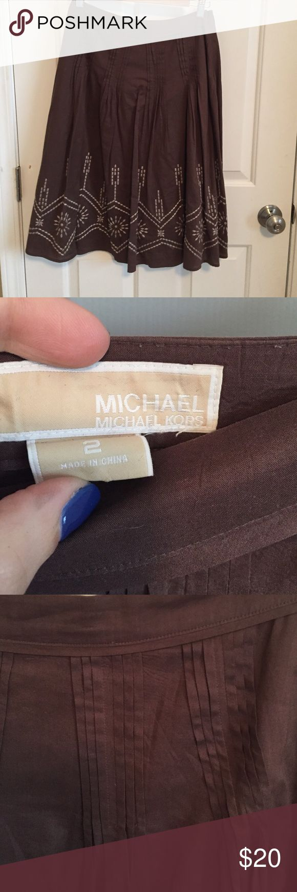 Michael Kors below knee lined skirt Michael Kors lined brown skirt has pleat work around waist line and then embroidery work around bottom.  Please let me know what questions you may have. Michael Kors Skirts A-Line or Full