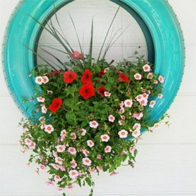 """I'm picturing this just propped in the corner of my flower bed. DIY tutorial on wall mounted and """"tire swing"""" flower planters."""