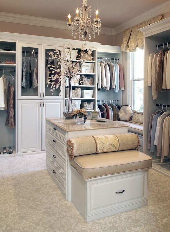 Isn't this master closet a dream? Crown molding, baskets, bench, chandelier, island, glass door inserts, marble countertop, raised panel, shelving, hanging: