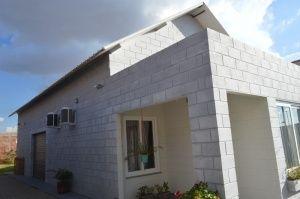 Por fora, os blocos de cimento à vista são aparentes e garante a aparência de imóvel industrial.