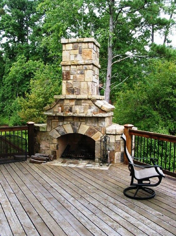 Stone stacked massive corner fireplace on wooden deck for Outdoor stone fireplace designs