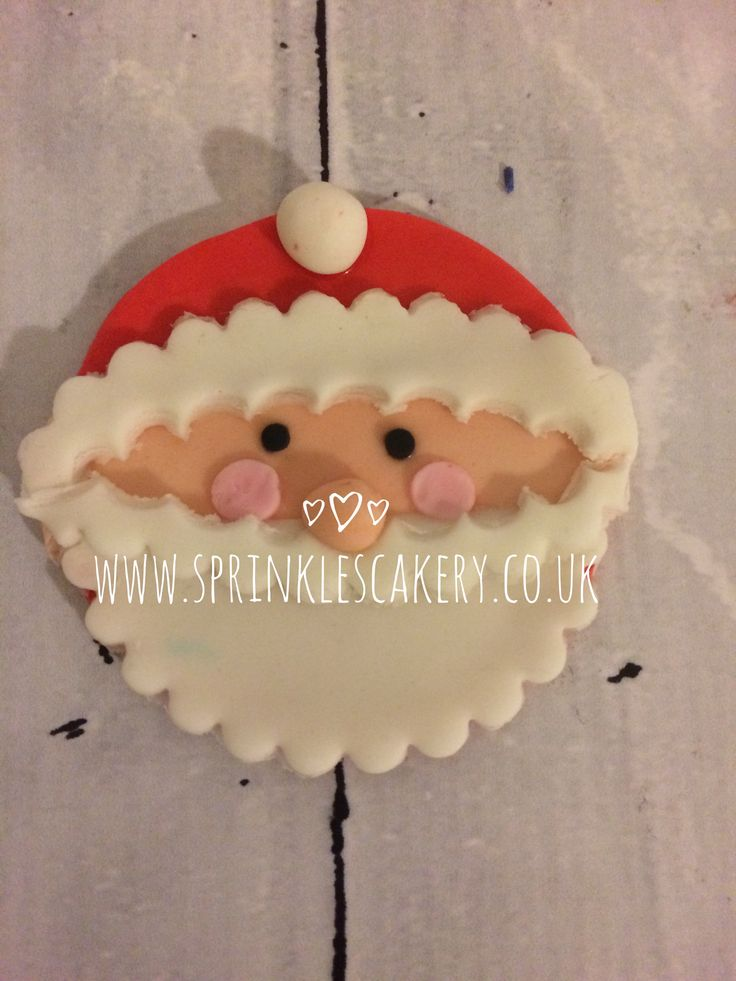 A Father Christmas head fondant cake topper.