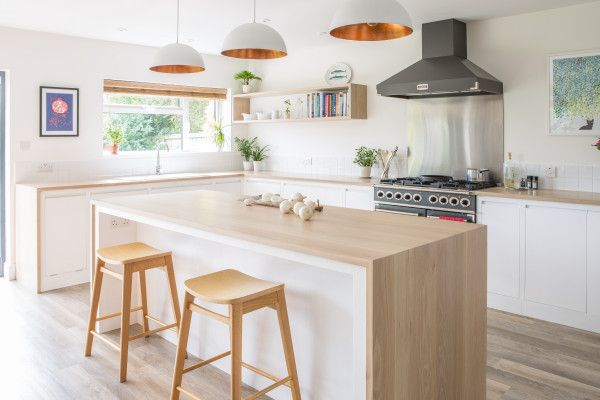 View of flat panel minimalist white kitchen with oak wrapped island and worktops