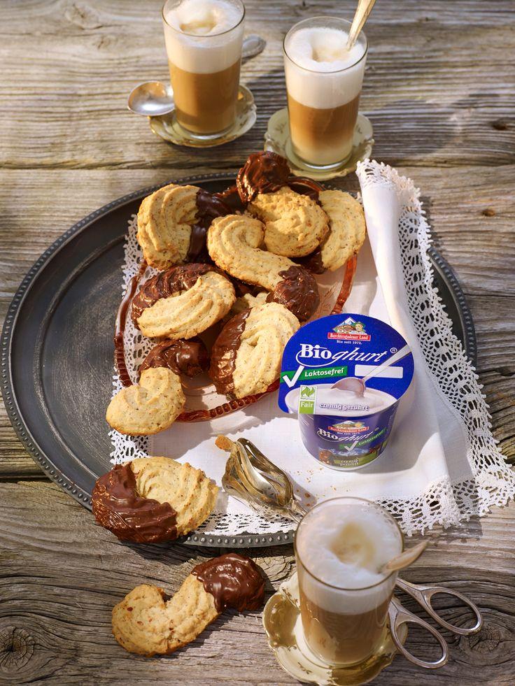 Joghurtspritzgebäck mit Bitterschokolade Zutaten für 30 Stück:    300 g Bergbauern-Butter  200 g Zucker  Salz  1 Bio-Zitrone (Schale)  1 Päckchen Vanillezucker  2 Eier  150 g Berchtesgadener Land Bio-Joghurt, Laktosefrei, 3,5 %  450 g Mehl  200 g Haselnüsse