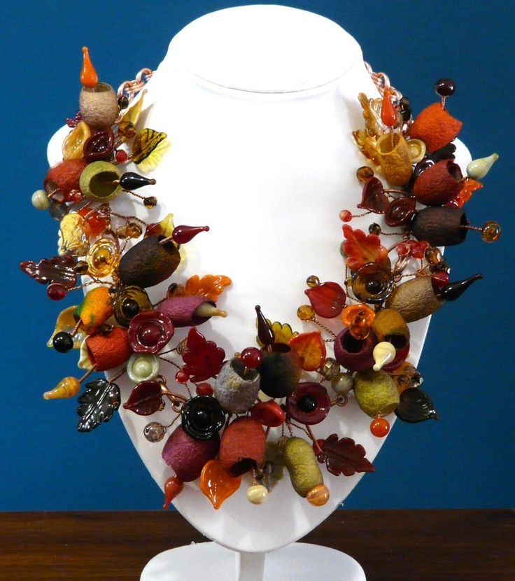 """Foliage"". Handmade lampwork glass leaves, flowers and buds, wired on to a copper base with dyed silk cocoons and czech crystals."