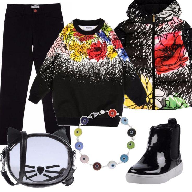 Questo outfit è firmato quasi tutto Moschino: comodi pantaloni a sigaretta neri, maxi-maglione in lana con stame colorate e piumino a base nera con la fantasia fiorata Moschino di questa stagione. Ai piedi, stivaletti impermeabili neri lucidi, per impreziosire il look. Un paio di accessori invece per sdrammatizzare: un bracciale colorato e una borsa in PVC trasparente, a forma di gattino.