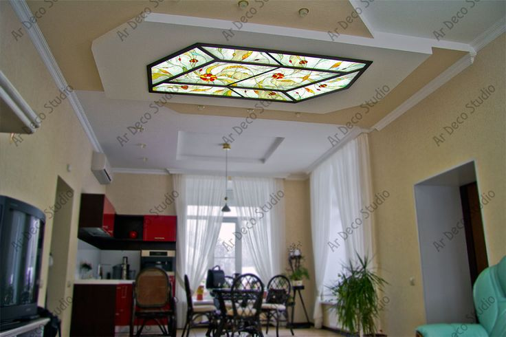 """Потолочный витраж """"Абстракция с красным акцентом"""" является центральным элементом комнаты. Сложная конфигурация потолков изначально предполагала абстрактный мотив в рисунке витража. Цвета панно объединяют бежевые стены, ярко-красный кухонный гарнитур и зеленые растения, любимые хозяйкой. Спечные элементы напоминают вкусные леденцы и, как нельзя кстати, вызывают аппетит. Размер 2,2х1,1 м. Студия художественного витража «Ар Деко», витражи21.рф, 8-919-672-4554, (8352) 29-33-63"""