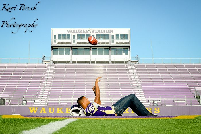 Kari Bruck Photography high school senior session pose idea for football players. High school senior boy inspiration for posing for football. Throwing up a ball laying on the 50 yard line on his football stadium. Sports or Sport pictures.